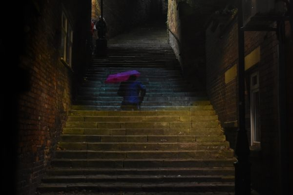 Projection teaser image man with red umbrella ascending the steps